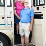 Happy Older Couple Standing In The Doorway Of Their RV