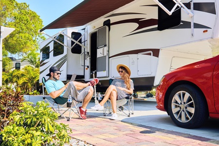 Couple Sitting Outside with RV and Car